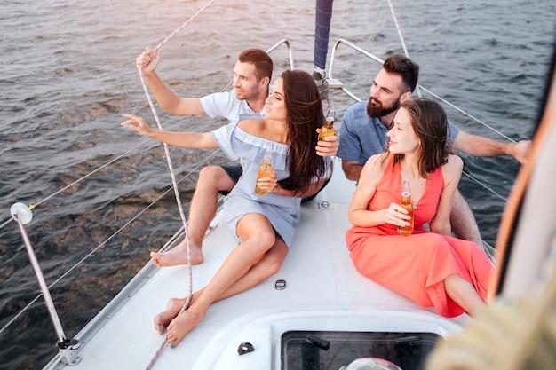 Das erste paar sitzt auf dem bug der yacht und schaut auf den sonnenuntergang