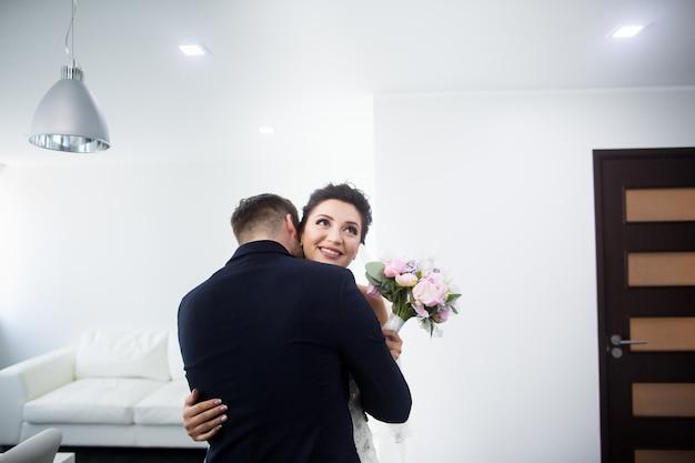 Das erste treffen. der bräutigam kommt mit einem blumenstrauß auf die braut zu.