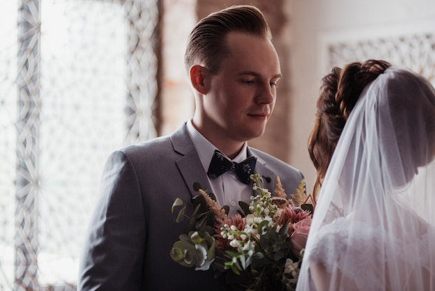 Das erste treffen. der bräutigam kommt mit einem blumenstrauß ins zimmer der braut. sie umarmen und küssen sich. rosa hochzeitskleid, grauer anzug und stilvoller blumenstrauß. zimmer im marokkanischen stil.