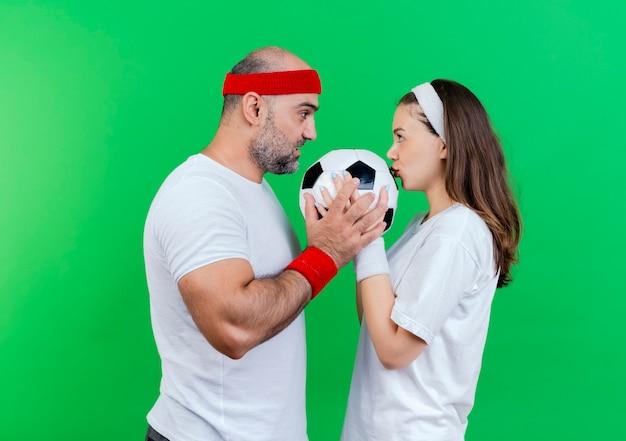 Das erwachsene sportliche paar, das stirnband und armbänder trägt, beeindruckte mann, der fußballfußballfrau hält, die ball küsst, der einander ansieht