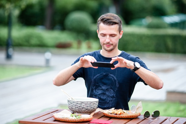 Das essen des jungen mannes nehmen nudeln auf der straße weg