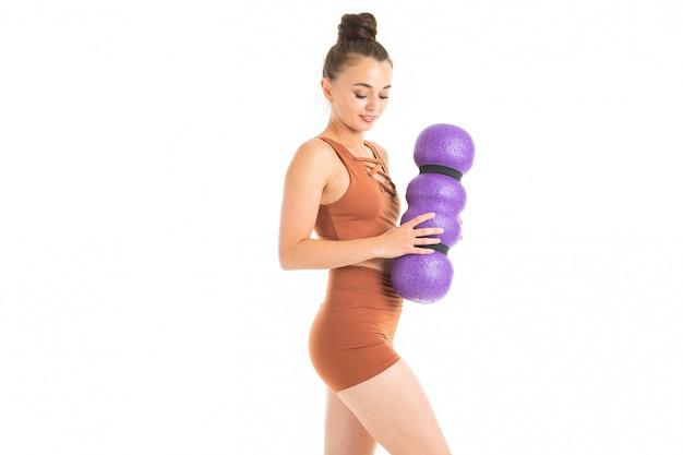 Das europäische brunettemädchen, das in einer braunen sportspitze und -kurzen hosen gekleidet wird, hält einen massager in ihren händen