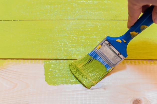 Das färben von holzoberflächen mit einem pinsel und acrylfarbe