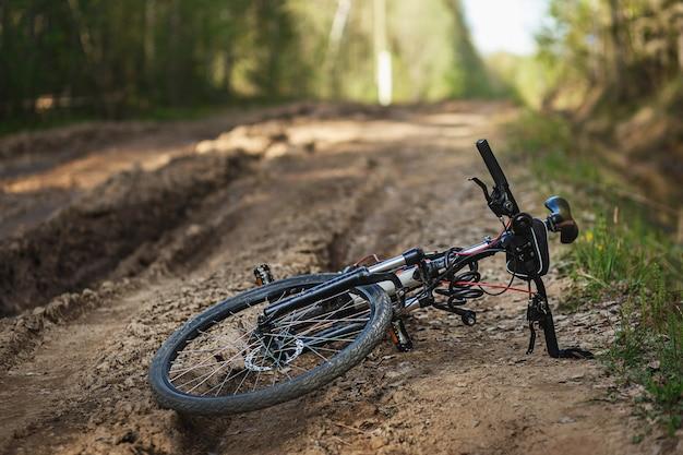 Das fahrrad liegt auf dem waldweg. asphaltreifen auf der schmutzigen forststraße. konzept der wahl mtb für das reiten auf dem lehm.