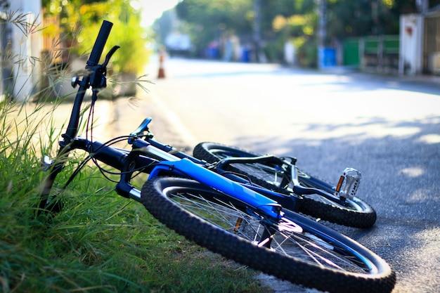 Das fahrrad wurde auf der asphaltierten straße im dorf abgestellt.