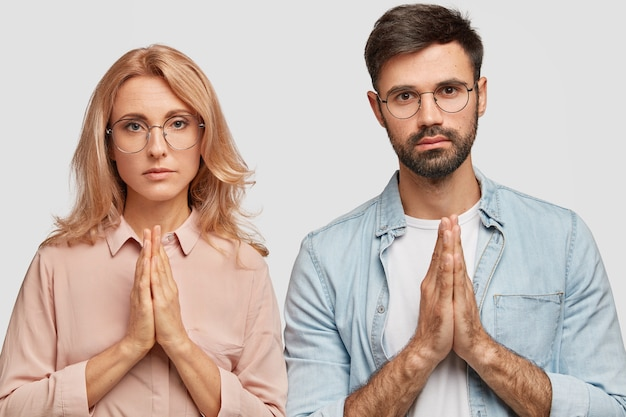 Das familienpaar steht in einer gebetsgeste und bittet gott, ihnen ein kind zu geben. hoffnungsvolle blonde frau kann nicht schwanger werden, glaubt an glück. attraktiver bärtiger junger mann wünscht sich etwas wünschenswertes