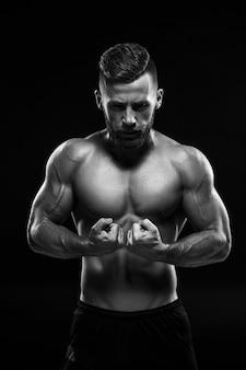 Das farblose bild des torsos des attraktiven männlichen bodybuilders auf schwarzem studiohintergrund.
