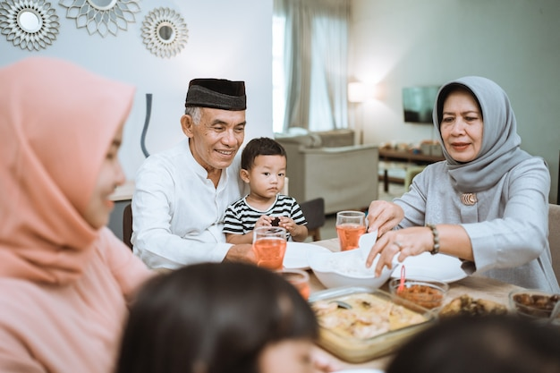 Das fasten brechen. muslimischer asiat mit hijab, der zusammen zu hause iftar-abendessen auf esstisch sitzt