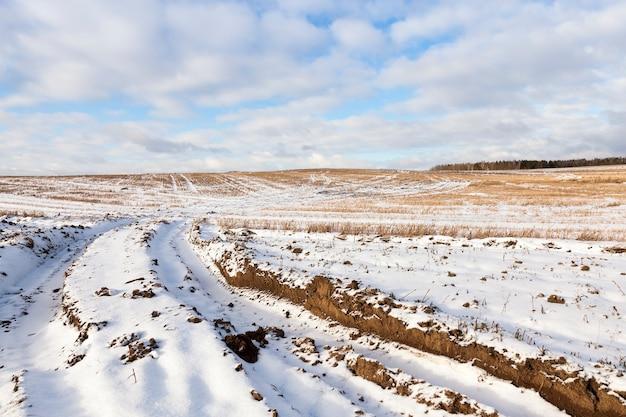 Das feld, in dem es spuren und spuren von autos gibt. in der winterzeit des jahres ist der boden nach einem schneefall mit weißem schnee bedeckt. nahaufnahme genommen