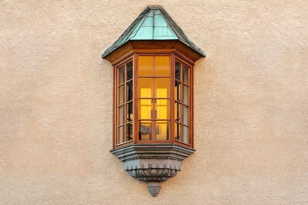 Das fenster in form eines erkerfensters befindet sich in der mitte der verputzten gebäudewand.