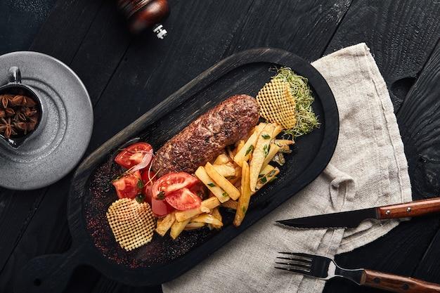 Das fertige gericht mit kebabfleisch und kartoffeln ist mit gemüse und gemüse dekoriert. das konzept von: frisches fleisch