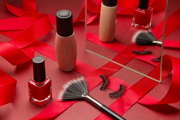 Das festliche make-up der frau mit grundierung, wimpern, make-up-pinsel und rotem nagellack mit spiegel und band