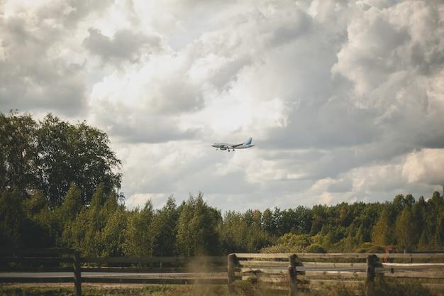 Das flugzeug fliegt über den wald. wolken im himmel