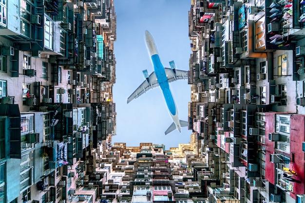 Das flugzeug fliegt über die montane mansion in der nähe von tai koo in hongkong. überfülltes altes retro-gebäude