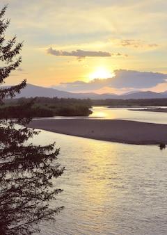 Das flussufer im altai-gebirge unter dem goldenen abendhimmel sibirien russland