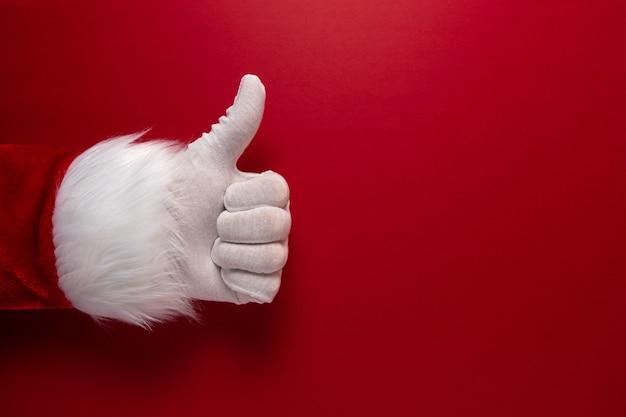 Das foto der behandschuhten hand des weihnachtsmanns zeigt den daumen nach oben