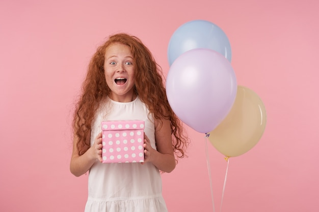 Das foto des freudigen kleinen mädchens mit dem roten lockigen haar, das elegantes weißes kleid trägt, das über rosa hintergrund aufwirft, geschenkbox verpackt hält, das über geburtstagsgeschenk aufgeregt wird, drückt wahre positive emotionen aus