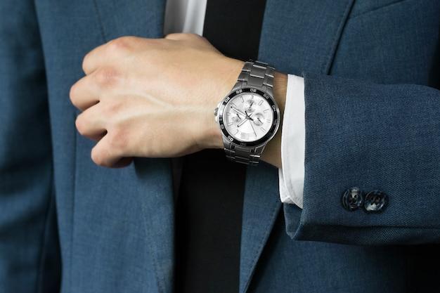 Das foto des geschäftsmannes im anzug. eine hand mit stunden
