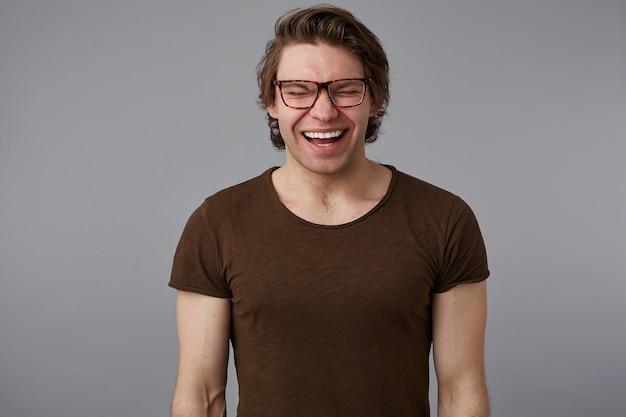 Das foto des jungen, gutaussehenden mannes mit brille trägt ein einfaches t-shirt, steht über grauem hintergrund und lächelt breit, sieht glücklich und verwundert aus.