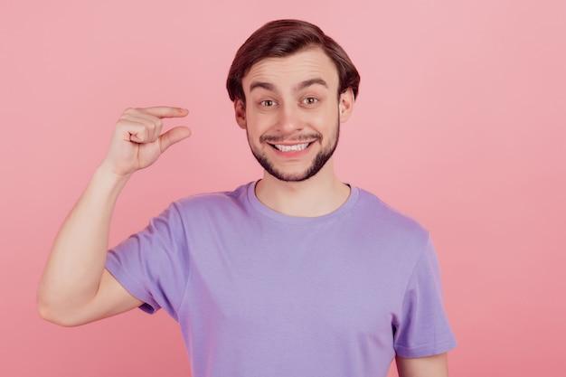 Das foto des jungen mannes glückliches positives lächeln zeigt winzige kleine maßnahmen mit fingern, die über rosafarbenem hintergrund isoliert sind