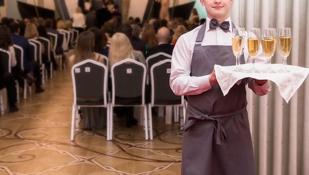Das foto des kellners bietet den gästen der veranstaltung champagner an