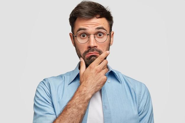 Das foto des überraschten bärtigen mannes hält das kinn und schaut zögernd, wundert sich über die neuesten nachrichten, trägt eine brille und ein elegantes blaues hemd, isoliert über der weißen wand. menschen- und mimikkonzept