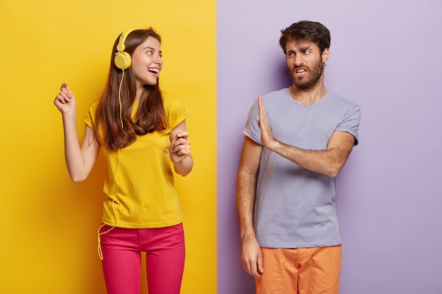 Das foto des unzufriedenen mannes zeigt eine stoppgeste, schaut unzufrieden auf eine frau, die musik in kopfhörern hört, spaß hat und bittet, sich ihr anzuschließen