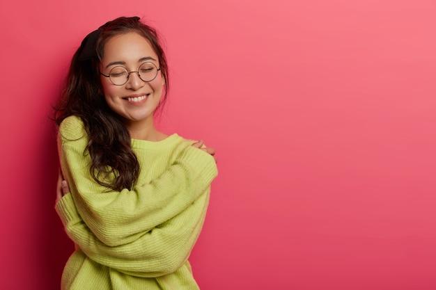 Das foto einer bezaubernden frau drückt selbstliebe und fürsorge aus, trägt gerne einen neuen weichen grünen pullover, umarmt den eigenen körper und erinnert sich an einen romantischen moment mit einem freund