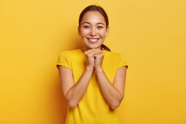 Das foto einer charismatischen asiatischen frau hält die hände in der nähe des kinns zusammen, lächelt sanft, hat einen niedlichen ausdruck, dunkles haar im pferdeschwanz gekämmt, trägt ein leuchtend gelbes t-shirt und wird in großartiger gesellschaft unterhalten