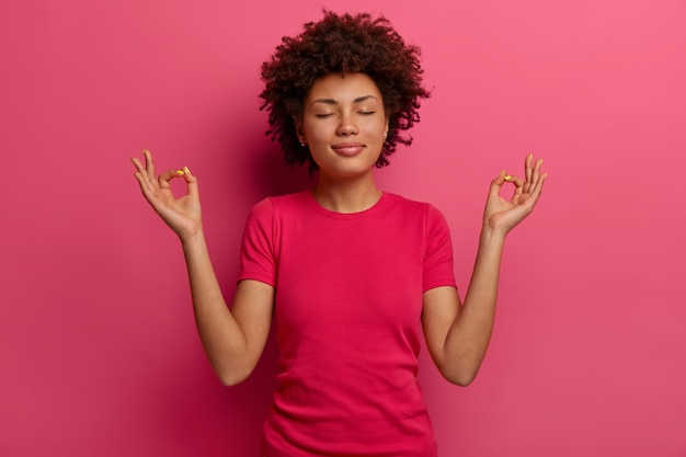 Das foto einer entspannten afroamerikanerin zeigt zen- oder ok-zeichen, meditiert in innenräumen, hat einen ruhigen ausdruck, schließt die augen, trägt ein lässiges t-shirt, hält geduld, praktiziert yoga-übungen und posiert in innenräumen