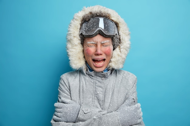 Das foto einer enttäuschten frau mit rotem gefrorenem gesicht weint, da es sich sehr kalt anfühlt, viel zeit im freien während eines strengen frostigen wintertages zu verbringen. graue oberbekleidung zittert und kuschelt sich. erholungskonzept