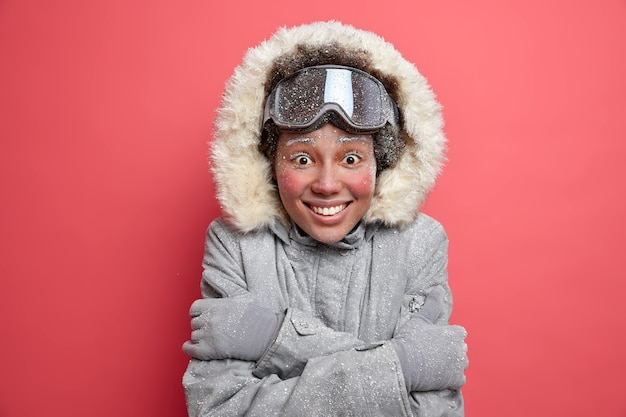 Das foto einer freudigen frau mit roten wangen, die von raureif bedeckt sind, umarmt sich und trägt eine warme thermojacke.
