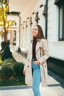 Das foto einer jungen frau, die lächelt, schaut weg nahe einem gebäude