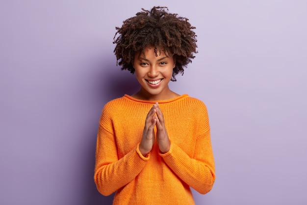 Das foto einer optimistischen dunkelhäutigen frau hat einen afro-haarschnitt, hält die handflächen zusammen, lächelt breit und ist zufrieden