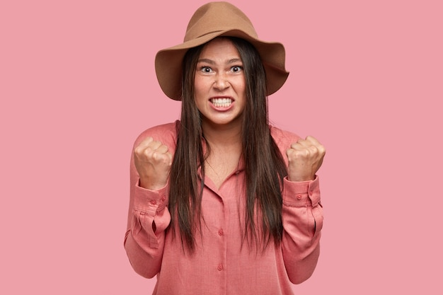 Das foto einer verärgerten, unzufriedenen, verärgerten freundin beißt zähne und fäuste zusammen und drückt wut aus, ebenso wie streit