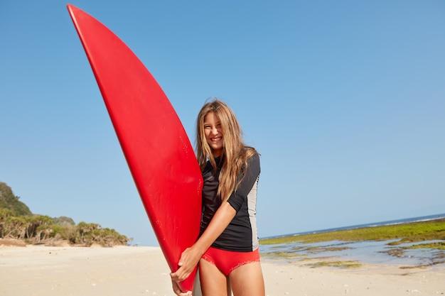 Das foto eines angenehm aussehenden glücklichen aktiven teenagers hält rotes surfbrett