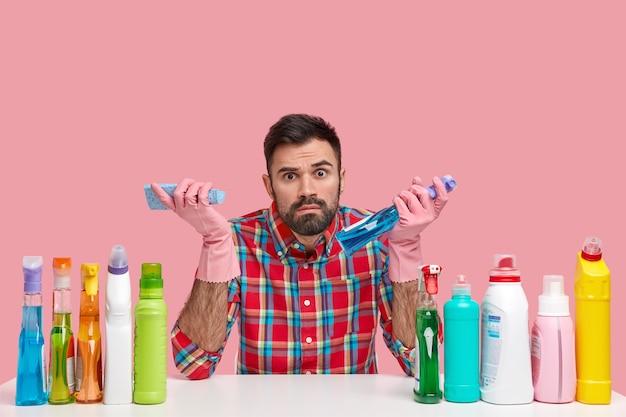 Das foto eines bärtigen mannes in kariertem hemd, der verschiedene reinigungsmittel verwendet, umgeben von plastikflaschen, sieht überraschend aus