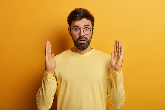 Das foto eines betäubten bärtigen mannes hebt beide handflächen, formt etwas sehr großes und breites, ist von großer größe begeistert, misst einen riesigen gegenstand, trägt eine transparente brille und einen lässigen pastellgelben pullover. zu viel