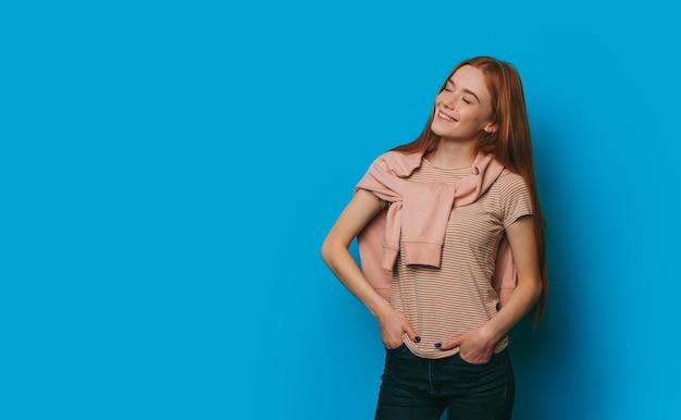 Das foto eines charmanten mädchens mittleren alters mit einem freudigen lächeln, das in einem netten t-shirt posiert, das von einem pullover bedeckt wird