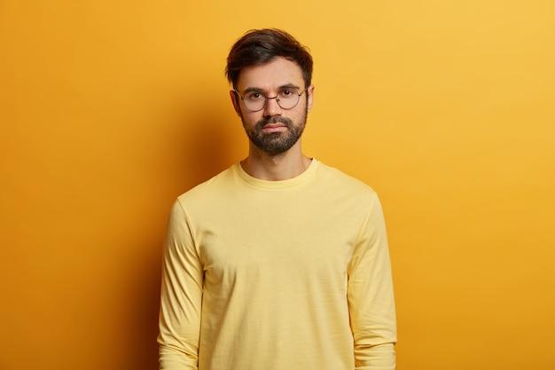 Das foto eines ernsthaft aussehenden mannes hat dunkle borsten, trägt eine runde brille und einen gelben pullover, einen direkten blick, posiert im haus und hat ein ungezwungenes gespräch mit jemandem. einfarbig. gesichtsausdruckskonzept