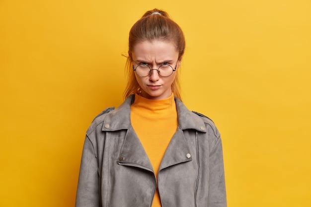 Das foto eines jungen hübschen weiblichen models sieht mit wütendem blick aus, ist irritiert von jemandem, der verrückt ist, nachdem er schlechte worte über sie gehört hat, und drückt negative gefühle aus.
