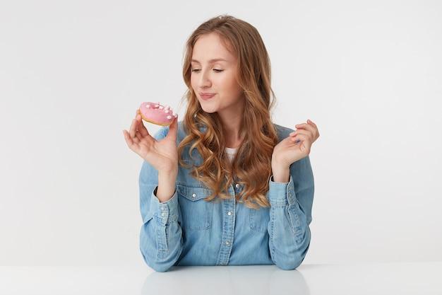 Das foto eines jungen niedlichen mannes, der ein jeanshemd mit langen blonden gewellten haaren trägt, betrachtet den donut in erwartung, wie es lecker und süß sein wird, ihn zu essen, isoliert über weißem hintergrund.