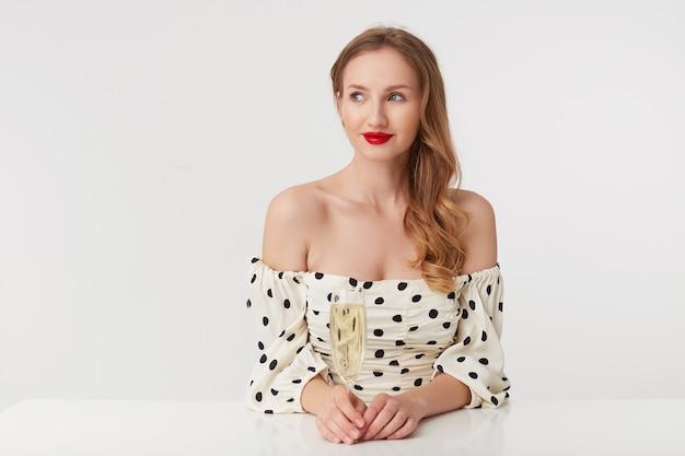 Das foto eines jungen schönen blauäugigen mädchens mit langen blonden haaren, mit roten lippen in einem gepunkteten kleid, das mit einem glas champagner am tisch sitzt, schaut spielerisch isoliert über weißem hintergrund weg.