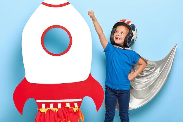 Das foto eines kleinen weiblichen kindes macht eine fliegengeste, gibt vor, superkraft zu haben, bereit für den flug und die rettung der welt, trägt einen umhang