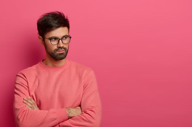 Das foto eines kontemplativen unrasierten mannes in einer brille hält die hände über der brust gekreuzt, denkt darüber nach, etwas interessantes für das projekt vorzubereiten, überlegt, wie man die situation löst, gekleidet in einen rosigen pullover