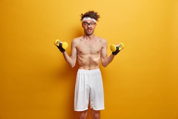 Das foto eines mageren mannes macht sport, baut zu hause muskeln auf, hat einen effektiven trainingskomplex mit hanteln, trägt weiße shorts und posiert mit nacktem oberkörper an der gelben wand. gesundheitskonzept
