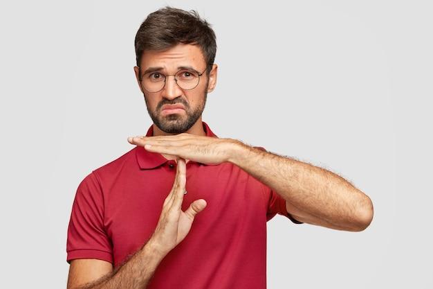 Das foto eines missfallenen bärtigen mannes hält die hände senkrecht, hat einen unsicheren ausdruck, versucht den weg oder die richtung zu erklären, trägt eine runde brille und ein rotes t-shirt, das über der weißen wand isoliert ist