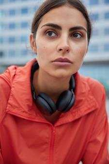 Das foto eines nachdenklichen weiblichen models denkt darüber nach, wie man nach dem lockdown zu den trainings zurückkehren kann, um körperliche aktivitäten im freien zu haben, trägt eine windjacke und blickt nach vorne