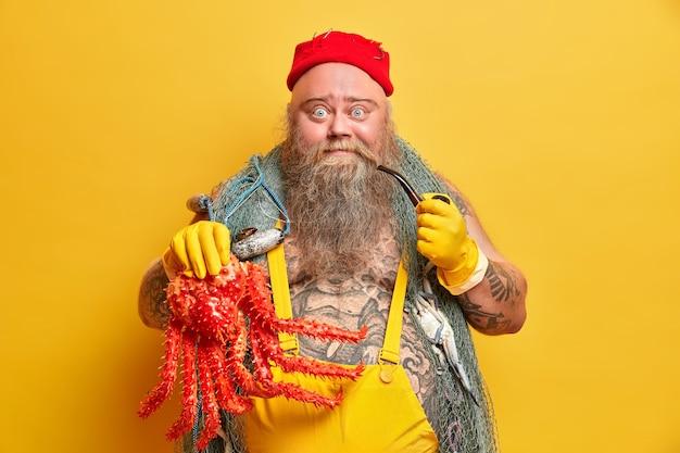 Das foto eines prallen bärtigen seefahrers, der einen großen roten tintenfisch gefangen hat, trägt ein in overalls gekleidetes fischernetz und hat einen tätowierten körper