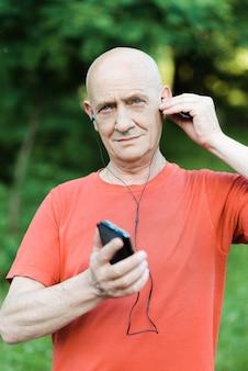 Das foto eines rentners im ruhestand trägt kopfhörer, während er musik hört und versucht, im park mitzuhören.